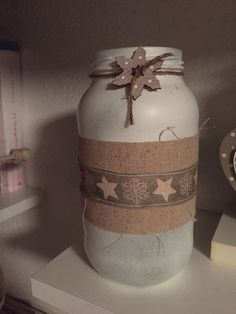Christmas Jar. Ho dipinto con una bomboletta spray bianca il barattolo.  Ho incollato un nastro e sopra ho sempre incollato un nastro con dei motivi natalizi. Infine con una cordicella ho legato il fiocco di neve in legno