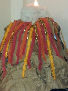 """The volcano I made for our """"Intergalactic Jurassic Adventure"""" camp theme. The underneath is made of different sized recycled boxes and the outside is crumpled grocery bags stapled/taped together and the lava is made from streamers and garland. The flame is one of those plug in fake flame lights and the smoke is cotton stuffing...we later replaced the flame with a 2 liter diet coke which when mixed with 5 mentose erupted 3 feet above the volcano!!!"""