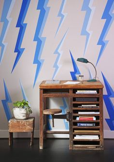 A home office with a bold lightning-bolt mural painted by Rory Hales and a vintage desk | archdigest.com