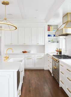 Exquisite white and gold kitchen is illuminated by a gold ring chandelier fixed over a white center island fitted with a microwave drawer and a farmhouse sink paired with an antique brass faucet mounted to a white countertop.