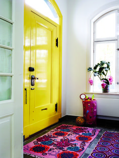"""My yellow door brings sunshine into my house year-round,"" says designer Charlotte Hedeman Gueniau. Also upbeat: the mismatched pair of patterned rugs. It can be tricky (and expensive) to find a rug custom-fit to your space, but a couple of smaller rugs does the job. For a yellow door: We like Valspar's Golden Delight, $31 a gallon, or Pratt & Lambert's Barleycorn, $22.99 a gallon. A high-gloss finish is rich and easy to clean."