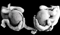 Black and white photo of twins held in their dad's strong hands.