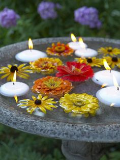 add flowers and floating candles to a birdbath