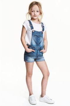 Bib overall shorts in washed stretch denim. Adjustable suspenders with metal fasteners, heart-shaped bib pocket with embroidery, and snap