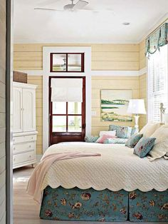 Sweet farmhouse cottage style.  Light yellow wood plank walls with pops of color.