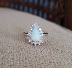This AMAZING Engagement Ring Features an 14k White Gold Setting. Set with a 1 Carat Natural Opal and Accented with .33 Carats of Brilliant Cut