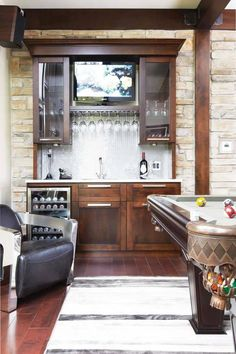 Basement bar cabinets form a sort of butler's pantry downstairs. A wine refrigerator, wet sink and counter top also house a TV to watch while playing pool on the leather / wood billiards table.