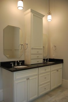 Master bath - custom designed and built double vanity with cabinet on top for extra storage, granite countertop, oval undermount sinks, chrome widespread faucets, and white carrara marble floors.