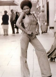 1973 Gloria Reynolds, a shop assistant on Kings Road, London. Funky chic in denim bell bottoms dungarees with a striped singlet and an Afro