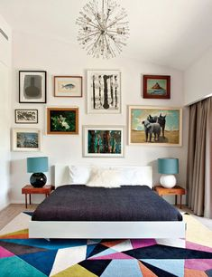 Love the colorful geometric rug, raw linen bed sheets, bedside tables, wall of frames... Everything! Plain white walls allow for daring and eclectic styling