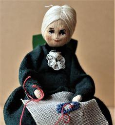 Charlotte Weibull - Broderande docka som sitter på en grön stol på