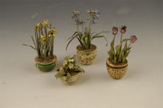 Four miniature cold painted metal pot plants by Beatrice Hindley, including daffodils, tulips, primrose and bluebells, each in a turned and decorated wood pot, three with remains of signature, 3.5in (9cm) the highest. (4)   Other examples of Beatrice Hindley's miniature plants, made in the 1920's can be seen in Queen Mary's doll's house at Windsor Castle.