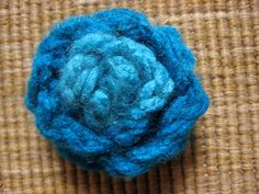 Child-made gift: finger knit brooch.  Maybe Viv can make one of these one day for her Uncle Luke - who loves brooches.