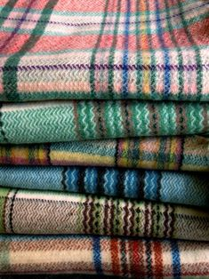 Colourful stack of tartan throws.