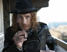 Paul Kaye ryger en cigaret (eller joint)