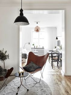 Swedish apartment // light pendants, leather butterfly chairs, wood flora and other minimal decor