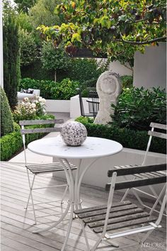 The white breakfast area looks past an eye-catching limestone sculpture to the main garden.