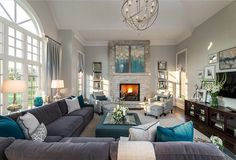 Living Room decor ideas - transitional style with gray and turquoise color palette. Gray velvet sectional sofa, patterned occasional chairs flank the stone clad fireplace, metallic globe light fixture and a blue upholstered storage ottoman functions as a coffee table.