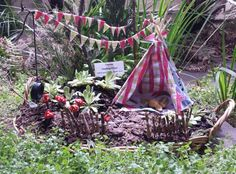 Fairy garden including lego wheel swing, mushroom ring, rustic picket fence, camp fire, teepee and bunting, and picnic bowls made from acorn tops.