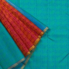 """The checkered """"Blue""""#handwoven Kanjivaram Silk Sari from Parisera is woven with peacocks and chakrams all over the body. A section of Ruby Red woven with peacocks and chakrams in zari make up the attractive pleats. An attractive zari adorn the pink pallu. The pink blouse completes the sari."""