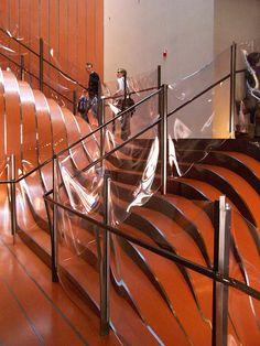 """""""Escada de metal, Nova York, 2006  O arquiteto Thomas Heatherwick usou tiras contínuas de aço laminado para montar a escadaria de uma loja de departamento em Nova York. Como o estabelecimento não fica no mesmo nível da rua, o desenho fluido e o material brilhante ajudam a atrair a atenção das pessoas para as compras"""". Via Casa Vogue"""