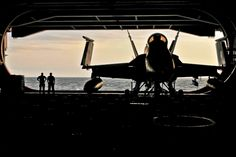 U.S. sailors watch the sunset from the hangar bay of the aircraft carrier USS Carl Vinson under way in the Arabian Sea, Jan. 21, 2012.