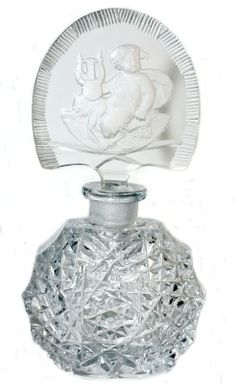 Morlee Crystal Perfume Bottle made in Czechoslovakia, with a stunning stopper featuring a Cherub. The beautiful bottle is deeply cut with diamond cuts and a starburst design on the front & back. The stopper has facet cuts along the outer edge, and still has it's original dauber attached. It has a frosted reverse intaglio of a Cherub and his Lyre Musical Instrument.