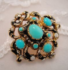 Gorgeous antique brooch from late Georgian to early Victorian period. The enameling is exquisite with designs done in black with white enamel. The design is repousse scrolling gold with extensive pierced work. The brooch is set with the best quality Persian turquoise cabochon stones. This brooch was once part of a full suite to make day earrings into night earrings.