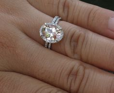 Oval peach sapphire engagement ring with diamond halo and band.