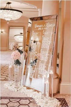 A wedding seating chart sign consisting of a framed mirror and calligraphy, tall glass vases with neutral and blush ranunculus bouquets and a garland of white flowers for a ballroom reception.