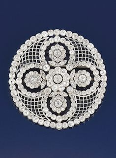 A Belle Epoque platinum and diamond cluster rosette brooch  Designed as a central quatrefoil of diamond circular cluster flowerheads with diamond line border and trelliswork detail, circa 1905, fitted case