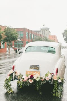 Getaway car with lush floral garland, I just love the idea of a vintage car for after the wedding. :)