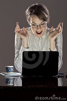 Young successful woman very excited by the info received on her laptop. Black laptop and cup of coffee on the desk.