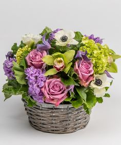 Garden Jewels - A perfectly seasonal collection of lavenders stock and roses, chartreuse green hydrangea and orchids, and white anemones are gathered in a rustic basket for a lush, gardeny feel.