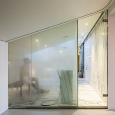 A marble-lined steam room is squeezed below the sloping ceiling of this apartment extension in Lisbon by local studio Camarim Arquitectos. Attic Bedroom Designs, Attic Rooms, Attic Spaces, Home Steam Room, Private Sauna, Lisbon Apartment, Condominium Interior, Penny Round Tiles, Marble Interior