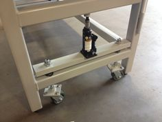 Retractable wheels: Hydraulic jack pushes crosspiece down/table up compressing the springs between crosspieces at wheel locations