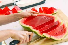 Now, it's just a matter of slicing! First cut each half into 1-inch slices, crosswise. | Here's How To Make XXL Watermelon Jell-O Shots