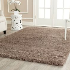 Cover up a bare area or conceal imperfections in your flooring with this polypropylene shag rug. You'll want to sink your toes into the high pile after a day spent on your feet. The taupe color keeps your living room decor classy and elegant.