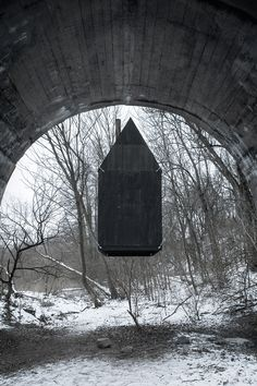 """At an abandoned military complex, beneath the arch of an old railway bridge, H3T Architekti built the """"Flying Black House"""". It"""
