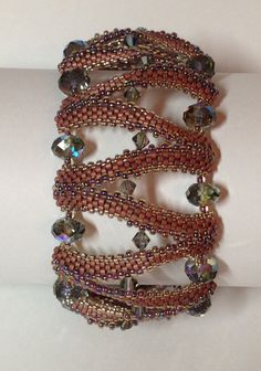 Stitch up this intricate looking bangle with three sizes of seed beads, and add sparkling crystal spacers. This bangle can also be made into