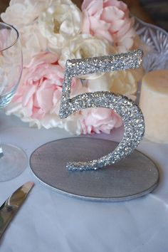 Add some sparkle and glam to your wedding reception with these glitzy glitter table numbers.  Dazzle your guests as you guide them to their assigned seating – guests will have no trouble finding their way to their tables with these sparkly little numbers!  Click here to see it in GOLD. To DIY: Use a stencil …