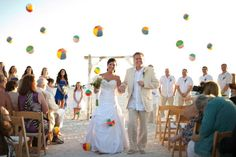 Beach wedding at the Post Card Inn on St Pete Beach FL. Beach balls being thrown over bride and groom. www.simpleweddingsflorida.com/postcardinn.html