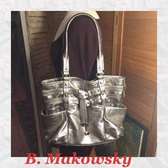 """LARGE B. MAKOWSKY SILVER METALLIC LEATHER TOTE CLASSIC HEAVY LEATHER WITH STURDY SILVER-TONED HARDWARE/MULTI COMPARTMENT B.MAKOWSKY TOTE. OWNER CARRIED ON VACATION IN MAY, SO NO MAJOR WEAR TO NOTE. UNDER SIDE SIGNATURE SILVER TAG, PEN MARK SIZE DING. PICTURED. COMES WITH SLEEPER BAG. ANIMAL PRINT MULTI COMPARTMENT INTERIOR! 11"""" DOUNLE STRAP DROP WITH REINFORCED SHOULDER CUSHION. BAG IS 12"""" HIGH BY 17"""" LONG BY 6"""" DEPTH. MAGNETIC CLOSE. LARGE WRAP EXTERIOR SIDE PICKETS. b. makowsky Bags Totes"""