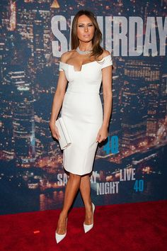 Melania Trump wearing a white off-the-shoulder dress and pointed toe pumps at the SNL 40th Anniversary Event.