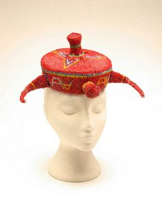 This red beaded hat comes from the Democratic Republic of Congo in central Africa. It has been made by the Pende people and is usually worn by a chief. Two horns stick out either side of the hat, and point forward. These are in imitation of buffalo horns and refer to the chief's authority - the chief is expected to be strong and powerful.  Find out more on our website www.objectlessons.org