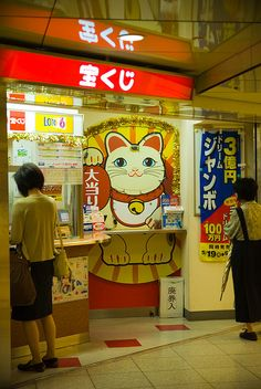 Japanese lottery stand(takara kuji)and Lucky cat(maneki neko)..;..    Note:Manekineko is a popular lucky cat(icon) which people place in the entrance halls of restaurants or shops.  such as daruma..