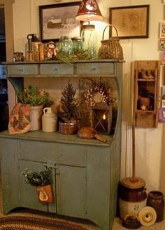 sage green cupboard with assorted wares