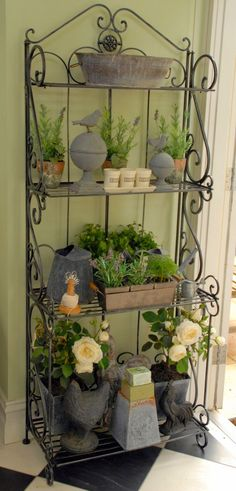 I always like a wrought-iron bakers stand. I use this to house all my gardening bibs and bobs, little herb pots and my collection of grey tin pots, urns and birds. It makes a great display for the door out to the garden.: