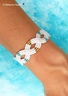 Macrame bracelet, infinity pattern, white, gold, aqua marine and turquoise. Adjustable. Available in my Etsy shop. © Natacha Fayard