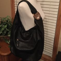 Super cute large black bag Large black shoulder bag. Has one zip side pocket with  two pouch pockets inside. One zip pocket on the outside. Snap enclosure brown lining. Outside of bag is excellent condition. Inside only has some spots on the lining from wear. Price reflects authenticity. Bags Shoulder Bags